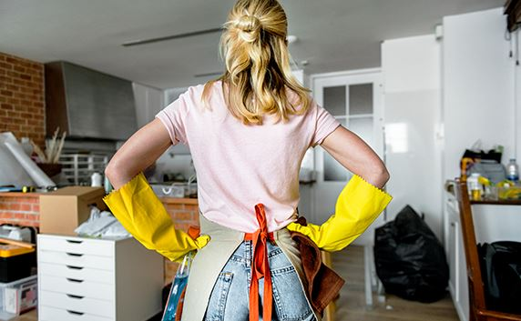 woman standing hands on hips cleaning inside house